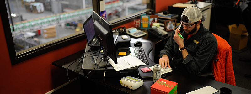 Joe Simmons talks on the phone at his desk on Tuesday, Jan. 12, 2016, at SweetWater Brewing Company in Atlanta, Ga. (AJ Reynolds for The Brewer Magazine)